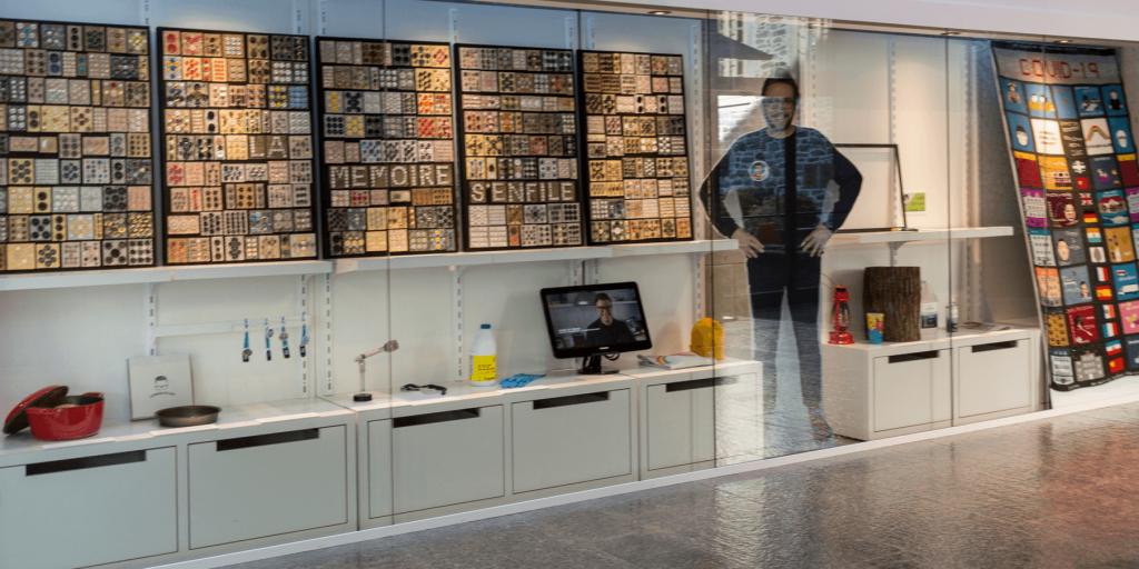 Photographie de la vitrine de l'exposition Documentez la pandémie, installée dans le hall du Musée. On y voit divers objets représentatifs du confinement.