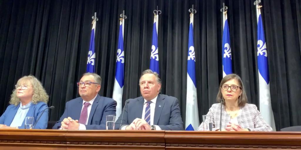Photo du Premier ministre du Québec, du directeur de la santé publique et d'autres ministres lors de la première conférence de presse au sujet de la COVID-19.