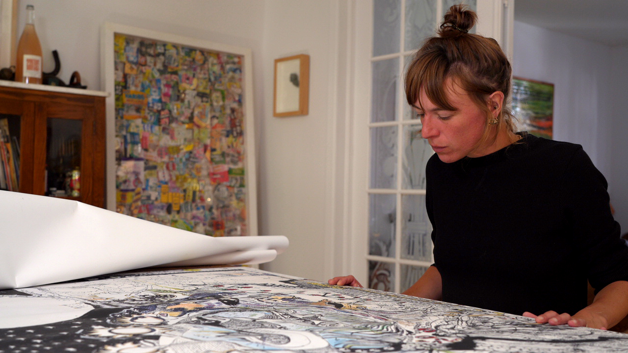Photographie de l'artiste Josée Landry Sirois à sa table de travail, chez elle.