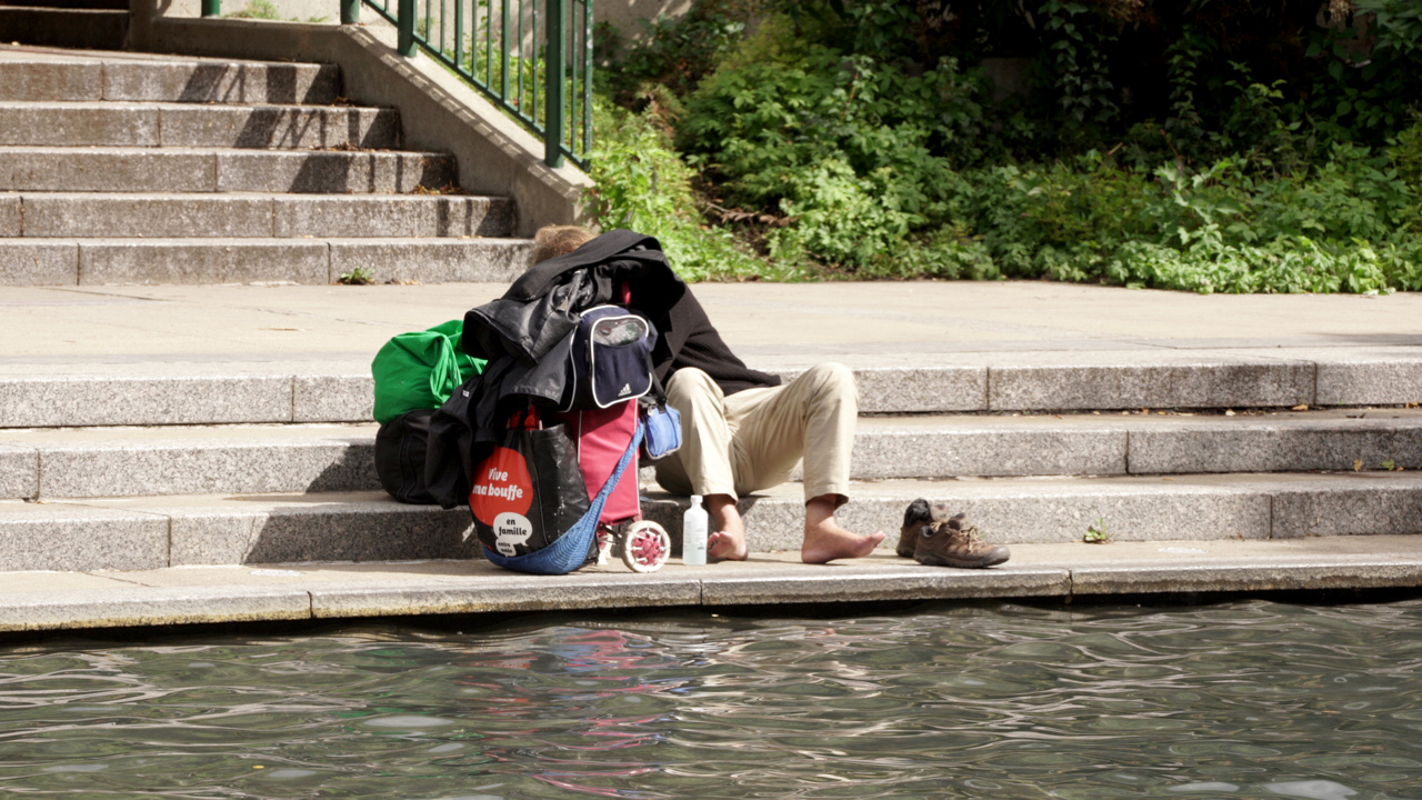 Photographie d'une personne en situation d'itinérance avec de nombreux bagages aux abords d'une étendue d'eau