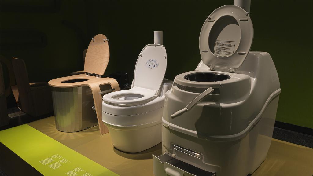 Photographie de trois toilettes sèches dans l'exposition ô merde!